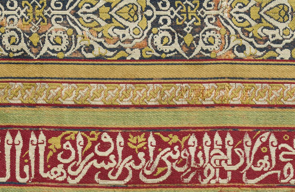 A 14th-century silk weaving decorated with stripes and an Arabic inscription.